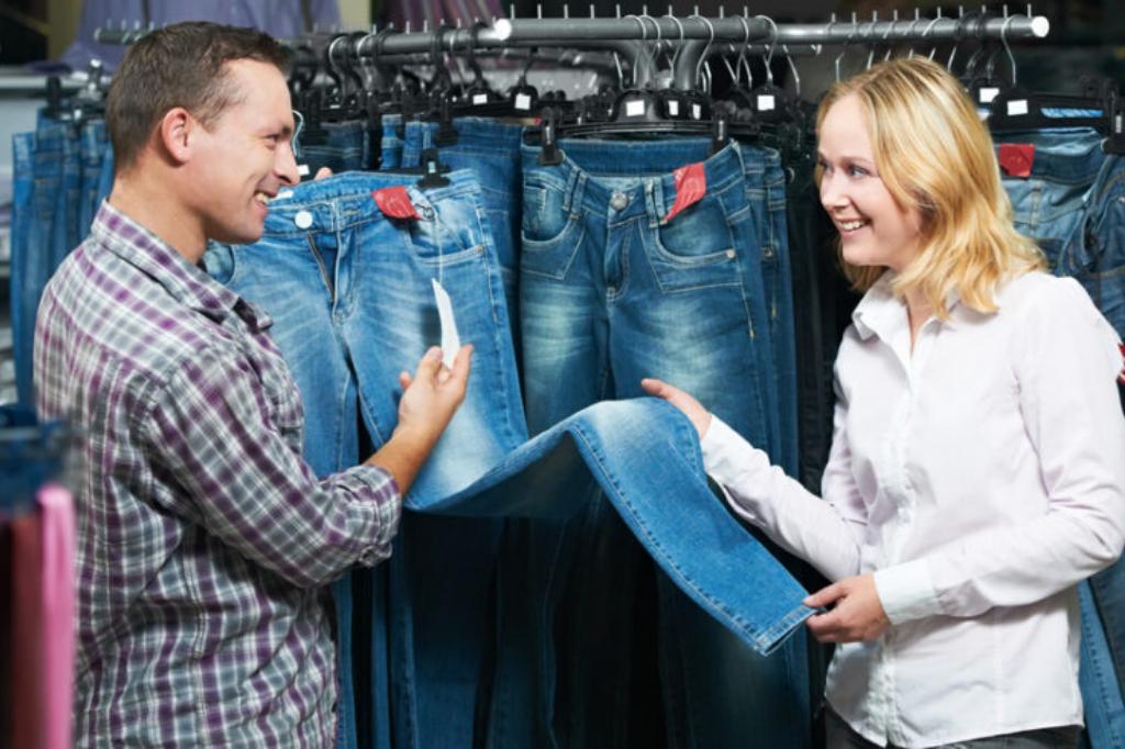 Женщина и мужчина выбирают джинсы в магазине