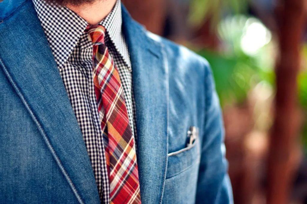 Мужчина в синем пиджаке и клетчатом галстуке